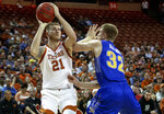 Texas forward Dylan Osetkowski (21) shoots over South Dakota State forward Matt Dentlinger (32) during a first round game of the NCAA college basketball National Invitation Tournament in Austin, Texas, Tuesday, March 19, 2019. (Nick Wagner/Austin American-Statesman via AP)