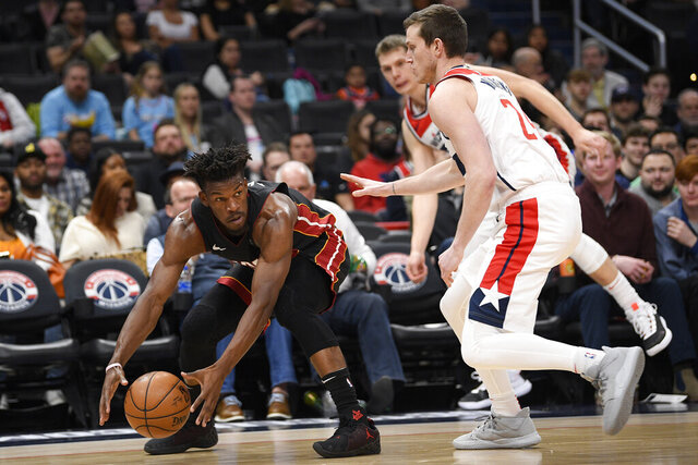 Miami Heat forward Jimmy Butler, left, grabs the ball next to Washington Wizards guard Garrison Mathews, right, during the first half of an NBA basketball game, Sunday, March 8, 2020, in Washington. (AP Photo/Nick Wass)