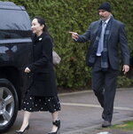 A security member points the way as Meng Wanzhou, chief financial officer of Huawei, leaves her home in Vancouver, Monday, January, 20, 2020. A court hearing begins today in Vancouver over the American request to extradite an executive of the Chinese telecom giant Huawei on fraud charges. (Jonathan Hayward/The Canadian Press via AP)