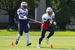New England Patriots running backs James White, left, and Rex Burkhead, right, work out with a flexible cord during an NFL football training camp practice, Tuesday, Aug. 18, 2020, in Foxborough, Mass. (AP Photo/Steven Senne, Pool)