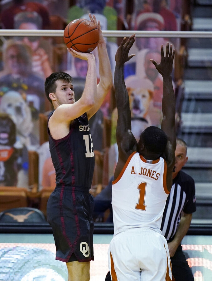Oklahoma guard Austin Reaves (12) shoots over Texas guard Andrew Jones (1) during the second half of an NCAA college basketball game Tuesday, Jan. 26, 2021, in Austin, Texas. (AP Photo/Eric Gay)