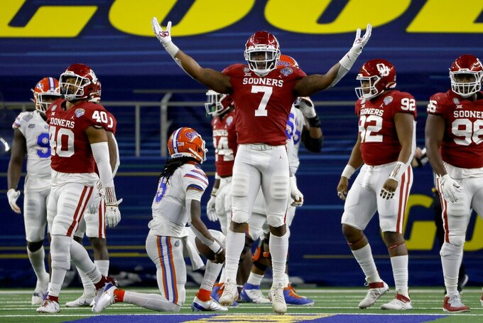 Oklahoma defensive end Ronnie Perkins (7) celebrates after sacking Florida quarterback Emory Jones, center left on knee, during the second half of the Cotton Bowl NCAA college football game in Arlington, Texas, Wednesday, Dec. 30, 2020. (AP Photo/Ron Jenkins)