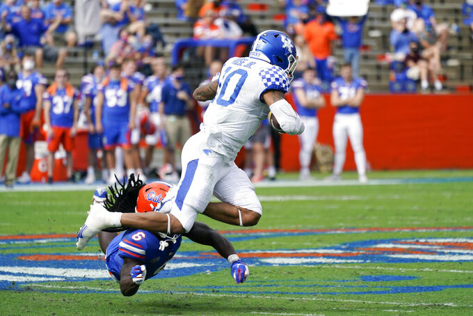 Kentucky running back Asim Rose Jr., right, tries to leap over Florida defensive back Shawn Davis (6) during the first half of an NCAA college football game, Saturday, Nov. 28, 2020, in Gainesville, Fla. (AP Photo/John Raoux)
