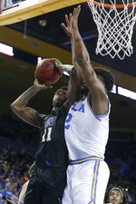 Washington guard Nahziah Carter, left, shoots over UCLA forward Cody Riley during the second half of an NCAA college basketball game in Los Angeles, Saturday, Feb. 15, 2020. (AP Photo/Chris Carlson)