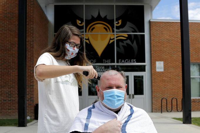 Maddie Shaner, left, a senior at Northeast Senior High School, shaves the head of Dan Calhoun, a local DJ and entertainer, while allowing graduating students to shave his head and wax his back and chest to fundraise for their senior prom, Saturday, May 16, 2020, in Pasadena, Md. Calhoun and a group of parents are taking it upon themselves to raise $10,000 it would cost to give the graduating class a prom in July after the school declined to free up the money for any gathering or activity due to the coronavirus outbreak. (AP Photo/Julio Cortez)