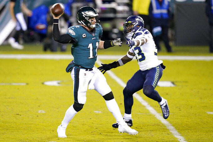 Philadelphia Eagles' Carson Wentz, left, passes against Seattle Seahawks' Jamal Adams during the first half of an NFL football game, Monday, Nov. 30, 2020, in Philadelphia. (AP Photo/Chris Szagola)