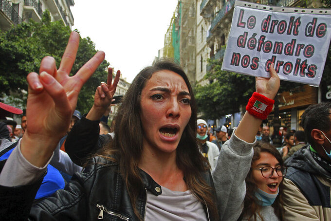 """Algerian students demonstrate, one with a poster reading """"The right to defend our rights"""" in Algiers, Tuesday, March 2, 2021. Protesters took to the streets of Algiers and other cities around Algeria last Friday in a bid to restart weekly pro-democracy demonstrations. (AP Photo/Fateh Guidoum)"""
