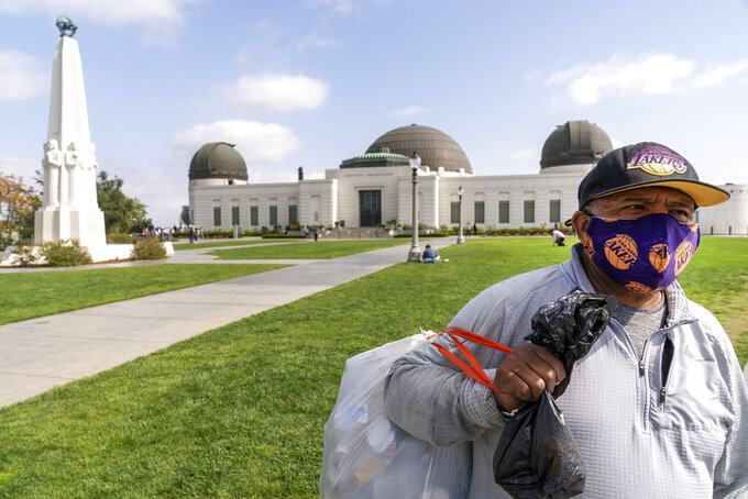 Jose Cartamo, 64, originally from El Salvador, wears a face mask as he collects recyclables at the Griffith Observatory in Los Angeles, Monday, May 17, 2021. Cartamo plans to make an appointment to be vaccinated. California is keeping its rules for wearing face masks in place until the state more broadly lifts its pandemic restrictions on June 15. (AP Photo/Damian Dovarganes)