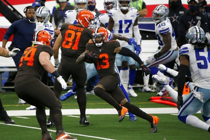 Cleveland Browns wide receiver Odell Beckham Jr. (13), makes his way through Dallas Cowboys defenders, past center JC Tretter (64) and Austin Hooper (81) on his way to the end zone for a touchdown late in the second half of an NFL football game in Arlington, Texas, Sunday, Oct. 4, 2020. (AP Photo/Michael Ainsworth)