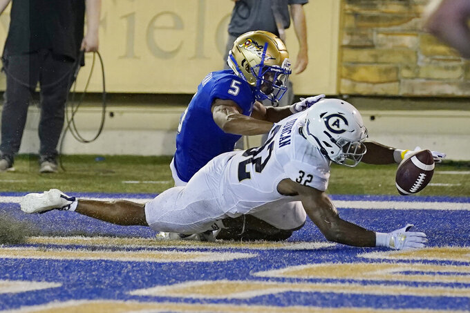 Tulsa's JuanCarlos Santana (5) and UC Davis' Erron Duncan (32) reach for a fumble by Tulsa's Keylon Stokes that rolled out of the end zone for a touchback during the second half of an NCAA college football game Thursday, Sept. 2, 2021, in Tulsa, Okla. (AP Photo/Sue Ogrocki)