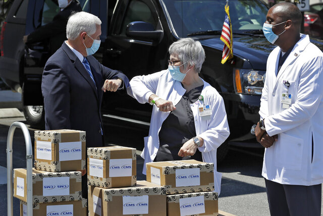 Vice President Mike Pence, left, greets director of nursing Shirley Schultz and health service administrator Fanley Romelus, right, after delivering personal protective equipment to the Westminster Baldwin Park, Wednesday, May 20, 2020, in Orlando, Fla., as part of the initiative to deliver PPE to more than 15,000 nursing homes across America. Pence is also scheduled to participate in a roundtable discussion with hospitality and tourism industry leaders to discuss their plans for re-opening the coronavirus outbreak. (AP Photo/Chris O'Meara)