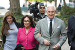 Roger Stone, and his wife Nydia, center, and daughter Adria, left, arrive at Federal Court for his federal trial in Washington, Thursday, Nov. 7, 2019.  (AP Photo/Cliff Owen)