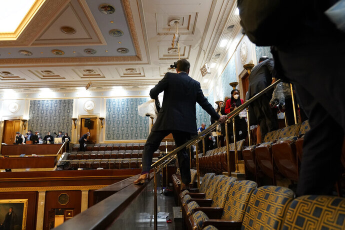 People shelter in the House gallery as rioters try to break into the House Chamber at the U.S. Capitol on Wednesday, Jan. 6, 2021, in Washington. (AP Photo/Andrew Harnik)