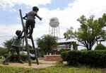In this Aug. 5, 2019, photo, a statue by a fountain just off the town square near the water tower is shown in Mount Vernon, Texas. In the small East Texas community Art Briles is coaching football again. Much further in many ways than the roughly 200 miles from Baylor, the school he led to the doorstep of the inaugural College Football Playoff five years ago and the school that fired him three years ago in the wake of a sprawling sexual assault scandal he has insisted he handled correctly. (AP Photo/Tony Gutierrez)