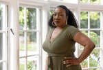 FILE - In this Oct. 13, 2020, file photo, Tarana Burke, founder and leader of the #MeToo movement, stands in her home in Baltimore. Since its launch in 2017, the #MeToo movement has experienced some fits and starts. But many associated with the movement have been buoyed by Gov. Andrew Cuomo's announcement that he's resigning amid a slew of sexual harassment allegations, seeing the outcome as a sign of the movement's durability. Burke says it's an encouraging sign that a younger, bolder generation of accusers is coming forward. (AP Photo/Steve Ruark, File)
