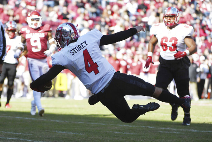 Western Kentucky quarterback Ty Story dives into the end zone to score a touchdown against Arkansas during the first half of an NCAA college football game, Saturday, Nov. 9, 2019 in Fayetteville, Ark. (AP Photo/Michael Woods)