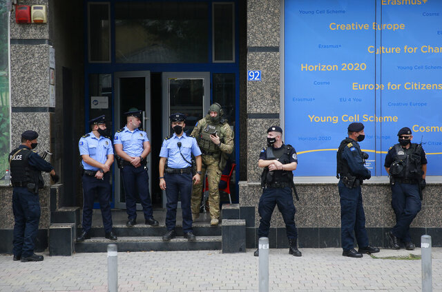 Kosovo police guard the entrance of the offices of a war veterans association in Kosovo, in Pristina, Friday, Sept. 25, 2020. Witnesses say European Union security police have stormed the offices of a war veterans association in Kosovo. The association represents the former ethnic Albanian separatists who fought Serbian troops in a 1998-1999 war for independence. Members of the group said police from the European Union Rule of Law Mission in Kosovo, or EULEX, prevented them from going into the association's offices in Pristina on Friday.  (AP Photo/Visar Kryeziu)