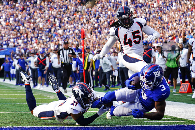 Denver Broncos' Ronald Darby (21) tackles New York Giants' Sterling Shepard (3) as Shepard scores a touchdown during the first half of an NFL football game Sunday, Sept. 12, 2021, in East Rutherford, N.J. (AP Photo/Matt Rourke)