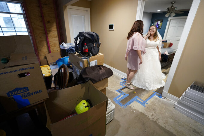 Nicole Caswell talks to her daughter Emily Pascale before her wedding, inside the home of Emily's now in-laws, Friday, Dec. 4, 2020,  Grand Lake, La., which was heavily damaged from Hurricanes Laura and Delta. (AP Photo/Gerald Herbert)