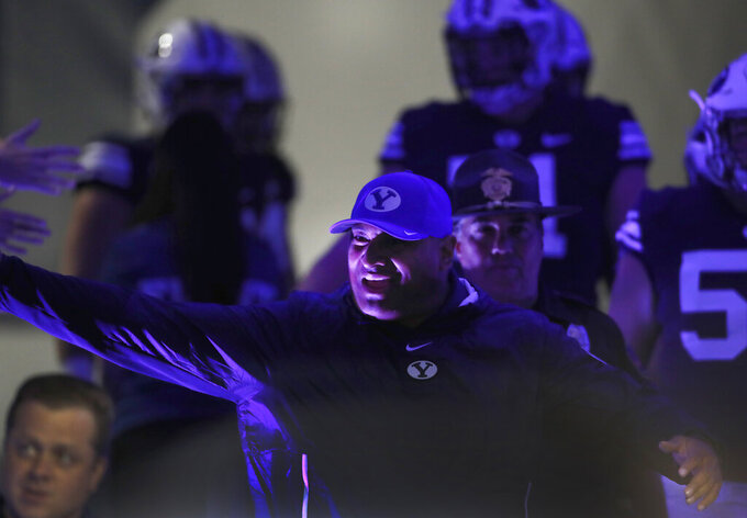 BYU head coach Kalani Sitake greets fans as he runs onto the field before an NCAA college football game against South Florida, Saturday, Sept. 25, 2021, in Provo, Utah. (AP Photo/George Frey)