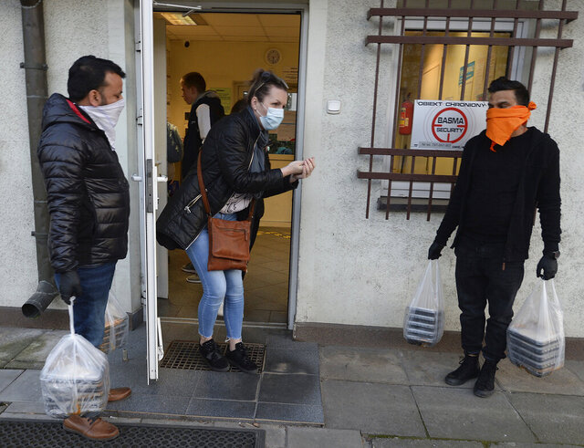 Staff of an Indian restaurant bring free meals for the doctors and medics of a contagious diseases hospital in a gesture of support for their hard work fighting the coronavirus, in Warsaw, Poland, Tuesday, March 17, 2020. For some people the new COVID-19 coronavirus causes only mild or moderate symptoms, but for some it can cause severe illness. (AP Photo/Czarek Sokolowski)
