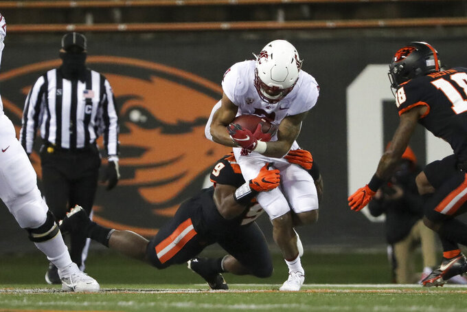 Washington State running back Deon McIntosh is brought down by Oregon State outside linebacker Hamilcar Rashed Jr. (9) during the first half of an NCAA college football game in Corvallis, Ore., Saturday, Nov. 7, 2020. (AP Photo/Amanda Loman)