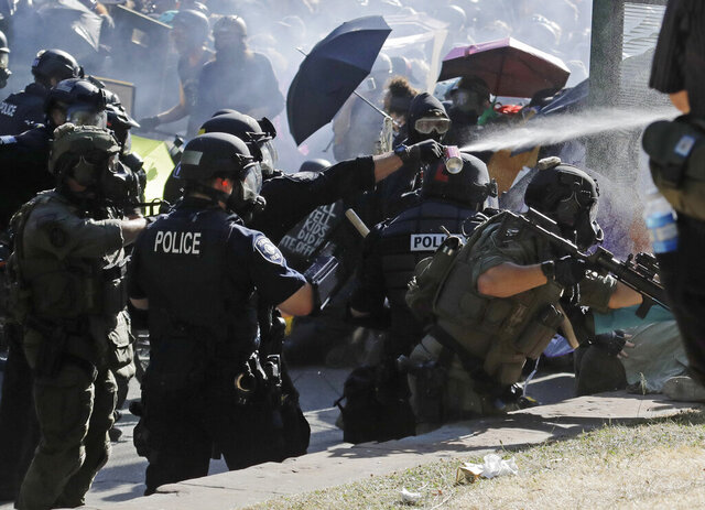 Police pepper spray protesters, Saturday, July 25, 2020, near Seattle Central Community College in Seattle. A large group of protesters were marching Saturday in Seattle in support of Black Lives Matter and against police brutality and racial injustice. (AP Photo/Ted S. Warren)
