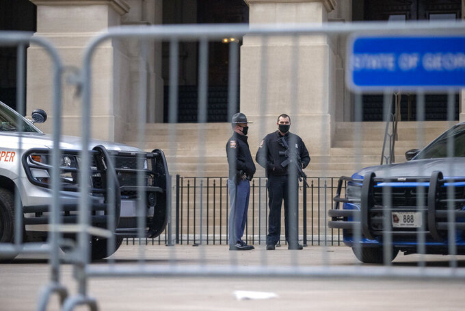 Georgia State Troopers stand guard in front of the Georgia State Capitol building on the first day of the 2021 legislative session in downtown Atlanta, Monday, Jan. 11, 2021. State capitols across the country are under heightened security after the siege of the U.S. Capitol last week. (Alyssa Pointer/Atlanta Journal-Constitution via AP)