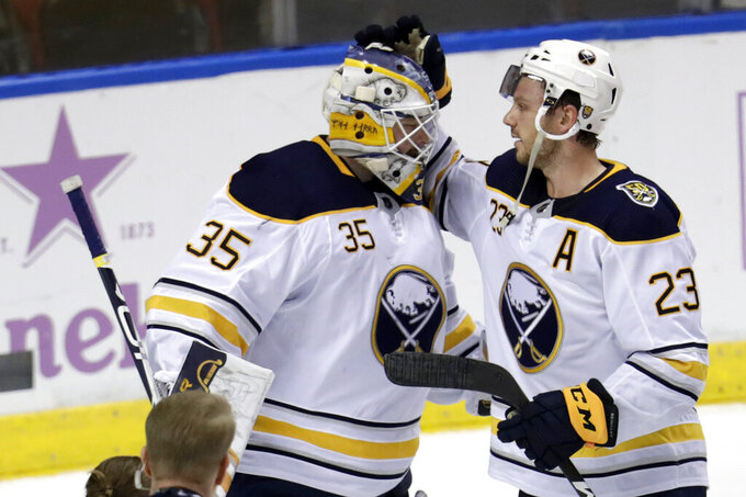 FILE - In this Nov. 24, 2019, file photo, Buffalo Sabres goaltender Linus Ullmark (35) is congratulated by center Sam Reinhart (23) after the Sabres defeated the Florida Panthers 5-2 in an NHL hockey game in Sunrise, Fla. On Sunday, Oct 25, 2020, Buffalo signed Reinhart to a one-year, $5.2 million contract, and Ullmark to a one-year $2.6 million deal.  (AP Photo/Lynne Sladky, File)
