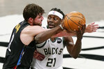 Brooklyn Nets forward Joe Harris (12) becomes entangled with Milwaukee Bucks guard Jrue Holiday (21) during the first half of Game 2 of an NBA basketball second-round playoff series, Monday, June 7, 2021, in New York. Harris was charged with a foul on the play. (AP Photo/Kathy Willens)