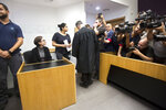 American Lara Alqasem, left, sits in a courtroom prior to a hearing at the district court in Tel Aviv, Israel, Thursday, Oct. 11, 2018. A senior Israeli cabinet minister on Wednesday defended the government's handling of the case of an American graduate student held in detention at the country's international airport for the past week over allegations that she promotes a boycott against the Jewish state. (AP Photo/Sebastian Scheiner)