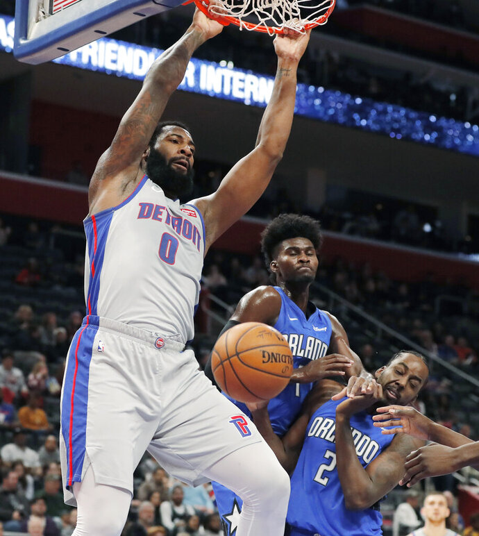 Detroit Pistons center Andre Drummond (0) dunks next to Orlando Magic forwards Jonathan Isaac (1) and Al-Farouq Aminu (2) during the first half of an NBA basketball game, Monday, Nov. 25, 2019, in Detroit. (AP Photo/Carlos Osorio)
