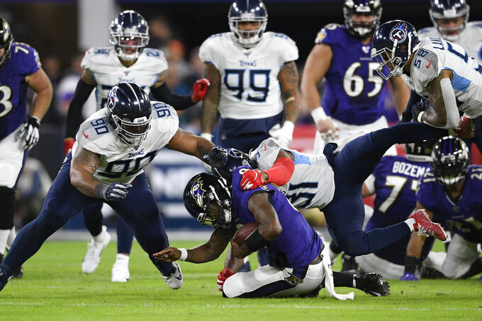 Baltimore Ravens quarterback Lamar Jackson (8) is hit by Tennessee Titans free safety Kevin Byard (31) and Tennessee Titans defensive end DaQuan Jones (90) during the first half an NFL divisional playoff football game, Saturday, Jan. 11, 2020, in Baltimore. (AP Photo/Nick Wass)