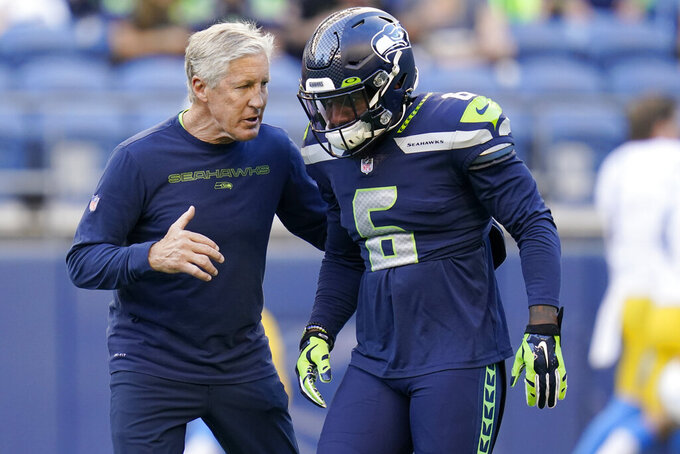 Seattle Seahawks head coach Pete Carroll, left, talks with strong safety Quandre Diggs before an NFL football preseason game against the Los Angeles Chargers, Saturday, Aug. 28, 2021, in Seattle. (AP Photo/Elaine Thompson)