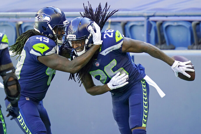 Seattle Seahawks cornerback Shaquill Griffin (26) is greeted by his twin brother, outside linebacker Shaquem Griffin (49), after Shaquill Griffin intercepted a pass against the Dallas Cowboys during the first half of an NFL football game, Sunday, Sept. 27, 2020, in Seattle. (AP Photo/Elaine Thompson)