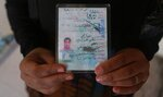 In this Feb. 26, 2019 photo, Nour Ahmed, who says says her husband was snatched by unknown assailants two years ago, displays her husband's identification card, at a legal clinic supported by the Norwegian Refugee Council, in west Mosul, Iraq. Thousands of Iraqi families face crushing social and legal discrimination -- including Ahmed -- all because of the choices their male relatives made under the Islamic State group's rule. (AP Photo/Khalid Mohammed)