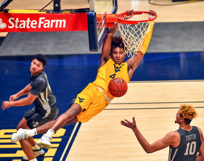 West Virginia guard Miles McBride (4) dunks against Iowa State during the first half of an NCAA college basketball game in Morgantown, W.V., Friday, Dec. 18, 2020. (William Wotring/The Dominion-Post via AP)