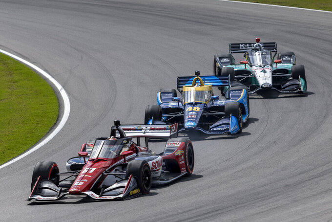 Ed Carpenter Racing driver Rinus Veekay (21) leads Andretti Autosport driver Ryan Hunter-Reay (28) and A.J. Foyt Enterprises driver Dalton Kellet (4) into turn two during the Honda Indy Grand Prix of Alabama auto race at Barber Motorsports Parkway, Sunday, April 18, 2021, in Birmingham, Ala. (AP Photo/Vasha Hunt)