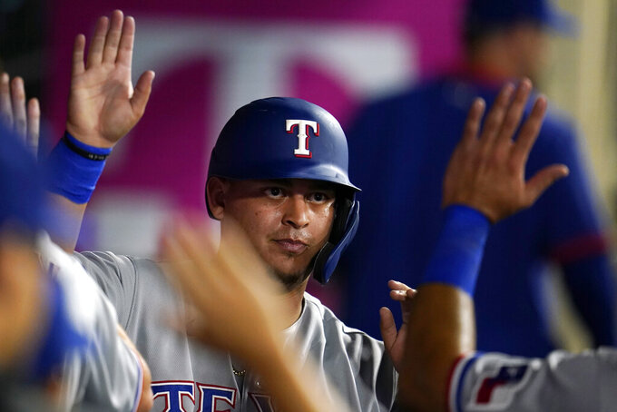 Texas Rangers' Yohel Pozo is high-fived in the dugout after scoring on a double by Jose Trevino during the seventh inning of a baseball game against the Los Angeles Angels Monday, Sept. 6, 2021, in Anaheim, Calif. (AP Photo/Marcio Jose Sanchez)