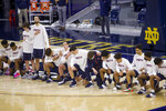 Members of the Virginia men's basketball team kneel during the national anthem before an NCAA college basketball game against Notre Dame on Wednesday, Dec. 30, 2020, in South Bend, Ind. (AP Photo/Robert Franklin)
