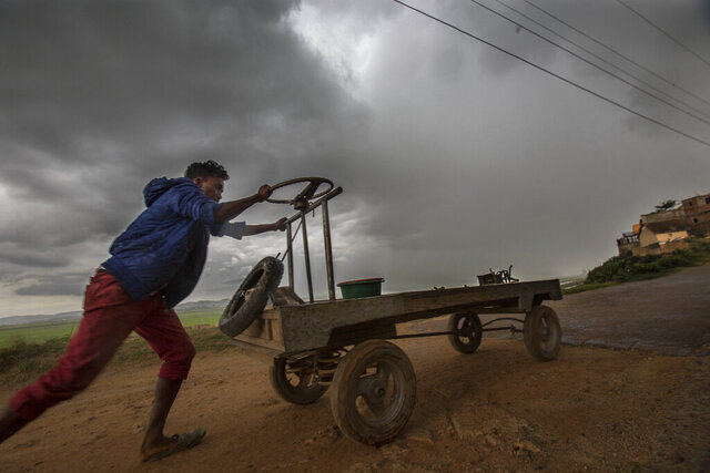 In this photo taken Monday, Dec. 9, 2019 a street vendor makes his way home under stormy skies in Antananarivo, Madagascar. Officials said Tuesday that Cyclone Belna has hit northern Madagascar, killing nine people and making more then 1,400 homeless. (AP Photo/Alexander Joe)