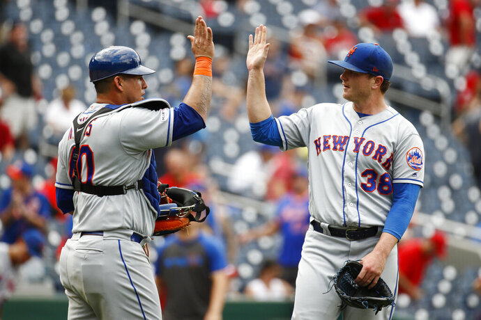 New York Mets catcher Wilson Ramos, left, and relief pitcher Justin Wilson high-five after closing out a baseball game against the Washington Nationals, Wednesday, Sept. 4, 2019, in Washington. New York won 8-4. (AP Photo/Patrick Semansky)