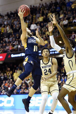 UNC-Greensboro guard Demetrius Troy (11) drives the ball to the basket against Wofford forward Keve Aluma (24) and forward Chevez Goodwin (1) in the second half of an NCAA college basketball game for the Southern Conference tournament championship, Monday, March 11, 2019, in Asheville, N.C. (AP Photo/Kathy Kmonicek)