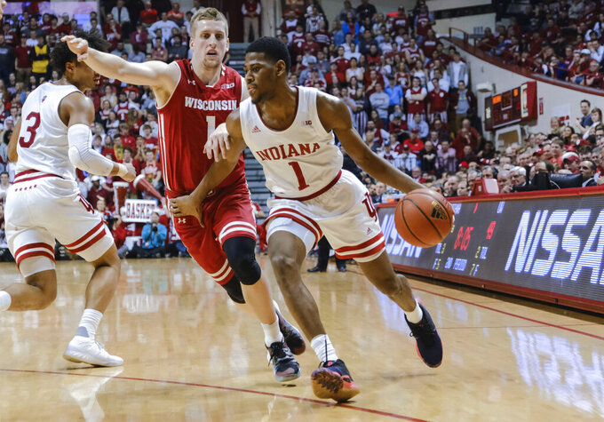 Indiana guard Aljami Durham, right, goes around Wisconsin guard Brevin Pritzl during the second half of an NCAA college basketball game in Bloomington, Ind., Tuesday, Feb. 26, 2019. Indiana won 75-73 in double overtime. (AP Photo/AJ Mast)