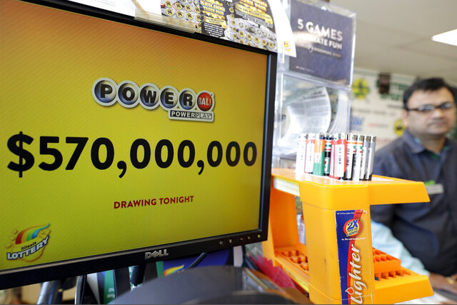 FILE - In this Jan. 6, 2018 file photo, a Powerball lottery sign displays the lottery prizes at a convenience store in Chicago. Lottery jackpots are going to shrink as the coronavirus pandemic tamps down lottery sales. The group that oversees the Powerball game announced Wednesday, March 25, 2020, that it would cut minimum jackpots in half, from $40 million to $20 million, after there is a winner of the current big prize. The jackpot also could grow more slowly, with minimum increases of $2 million instead of the normal $10 million after each twice-weekly drawing. (AP Photo/Nam Y. Huh File)