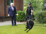 Britain's Prime Minister Boris Johnson, left, speaks to Sergeant Dog Handler Mike Barnes as he throws a ball for six year old cocker spaniel Rebel, a proactive drugs dog, during a visit to Surrey Police headquarters in Guildford, England,  Tuesday July 27, 2021. (Yui Mok/Pool Photo via AP)