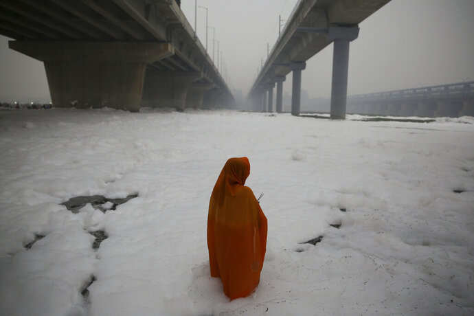 FILE - In this Saturday, Nov. 2, 2019, file photo, an Indian Hindu devotee performs rituals in the Yamuna river, covered with chemical foam caused by industrial and domestic pollution, during Chhath Puja festival in New Delhi, India. Schools have reopened in the Indian capital with toxic air level coming down by more than half since authorities declared a health emergency last Friday.  Authorities are tackling a large amount of toxic foam floating in the Yamuna River, caused partly by high ammonia levels emanating from industrial pollutants. (AP Photo/Altaf Qadri, File)
