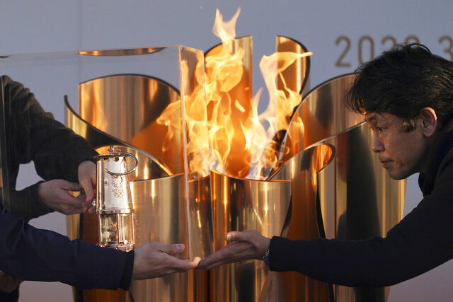 FILE - In this March 25, 2020, file, photo, officials light a lantern from the Olympic Flame at the end of a flame display ceremony in Iwaki, northern Japan. Before the Olympics were postponed, Japan looked like it had coronavirus infections contained, even as they spread in neighboring countries. Now that the games have been pushed to next year, Tokyo's cases are spiking, and the city's governor is requesting that people stay home, even hinting at a possible lockdown. (AP Photo/Eugene Hoshiko, File)