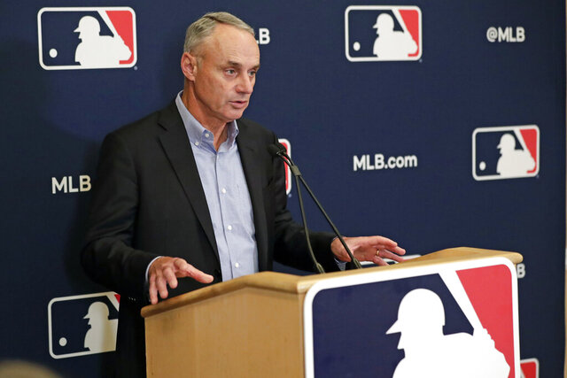 FILE - In this Feb. 6, 2020, file photo, Baseball Commissioner Rob Manfred answers questions at a press conference during baseball owners meetings in Orlando, Fla. Manfred tells The Associated Press that the commissioner's office, teams and the players' association