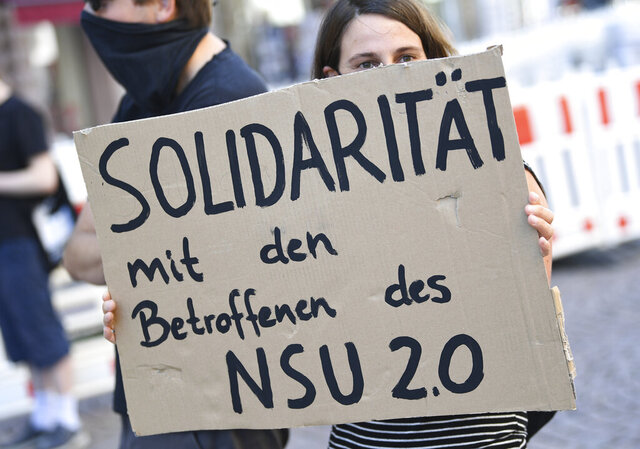 A demonstrator holds a poster with the inscription 'Solidarity with those affected by NSU 2.0'  during a rally in downtown Wiesbaden, Germany, Tuesday, July 21, 2020. Frankfurt prosecutors said a 63-year-old former police officer and his 55-year-old wife, were detained Friday in the Bavarian town of Landshut in connection threatening mails against several politicians signed 'NSU 2.0.' (Arne Dedert/dpa via AP)